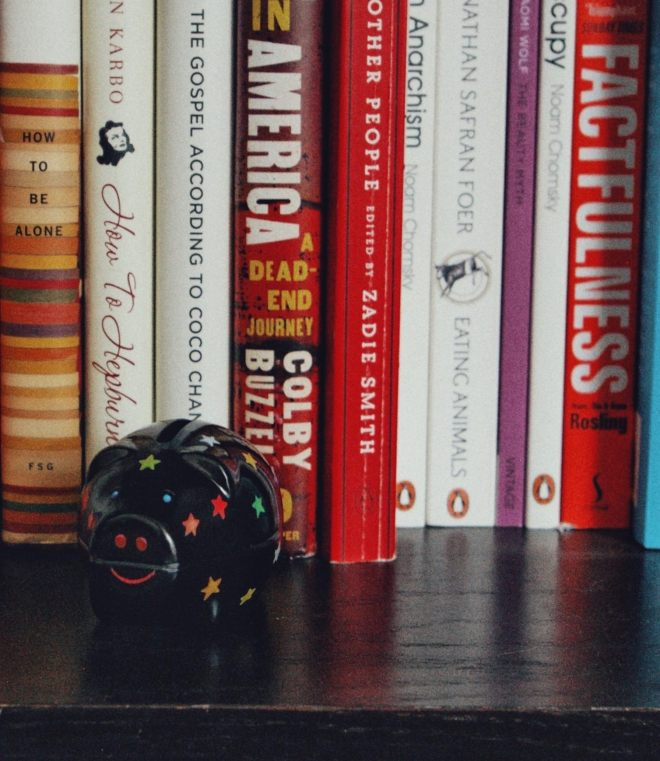black piggybank on a shelf and several books in the background