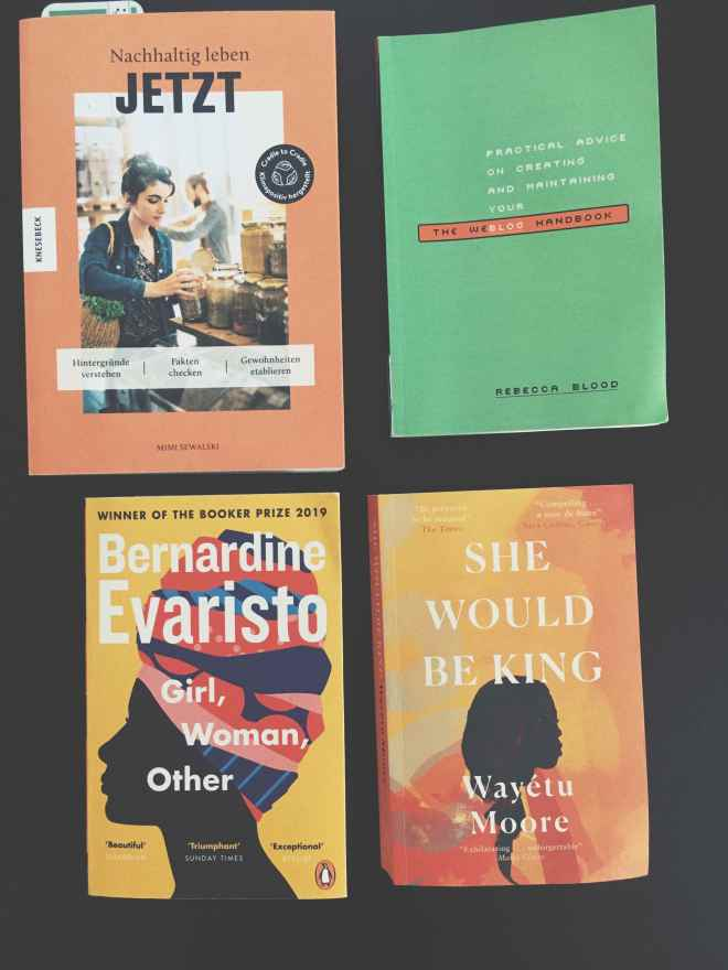 four books on a black table, three english titles, one german title