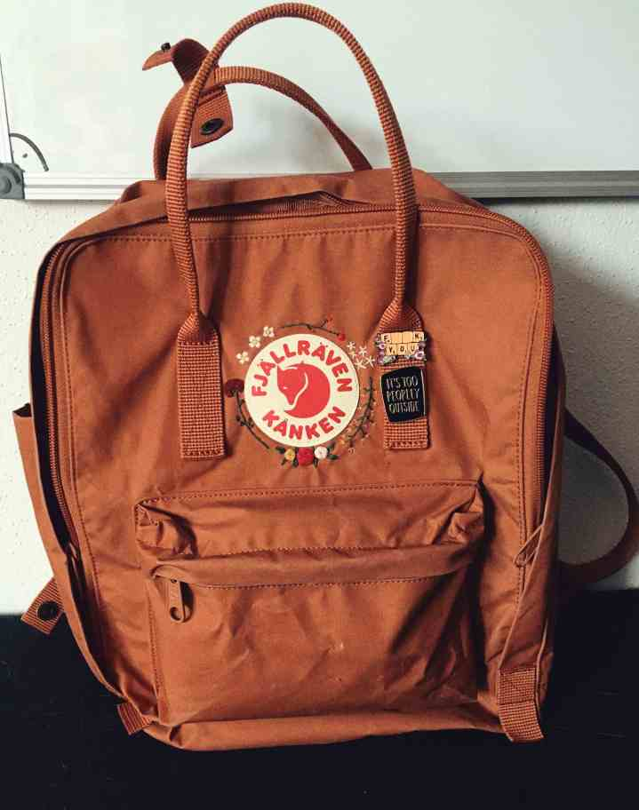 a fjällräven Kanken in color brick with embroidery and pins