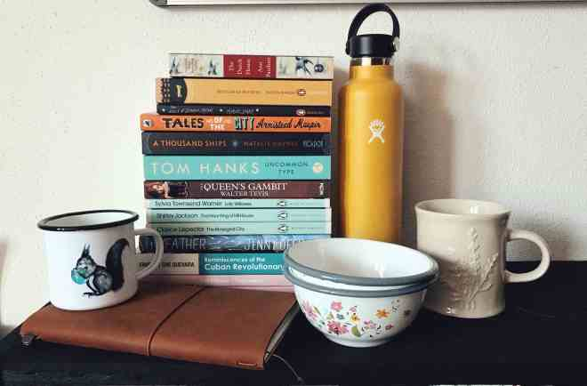 A pile of books, a hydroflask bottle, two cups, two bowls and a Midori traveler's notebook in camel on a shelf