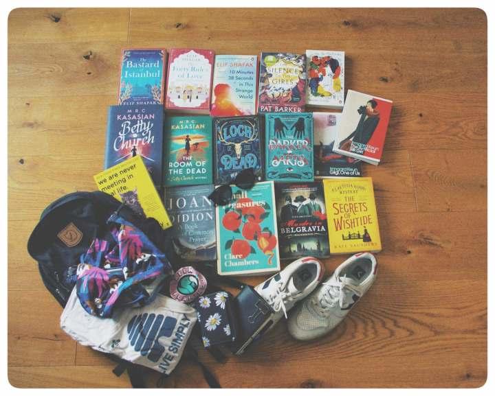 Bücher, schuhe, shirt, rucksack, notizbuch und geldbörse aufgelegt am boden