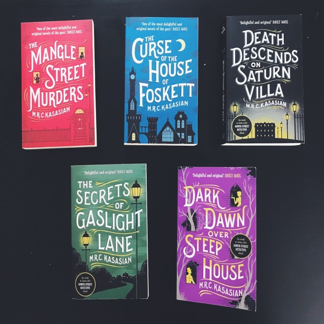 five book covers flatlay black background